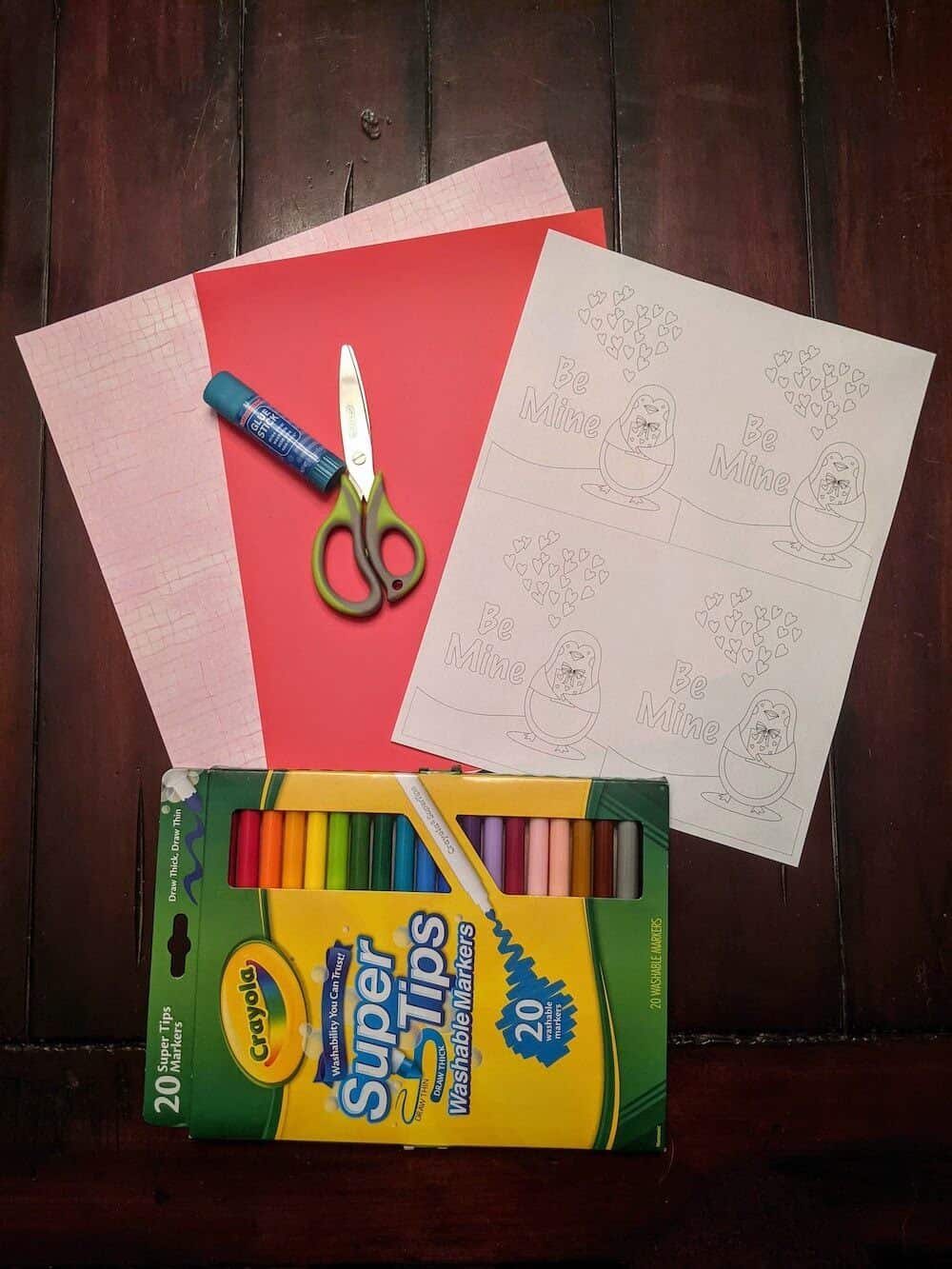 Printed penguin Valentine's cards with papers, scissors, glue stick, and markers ready for DIY project