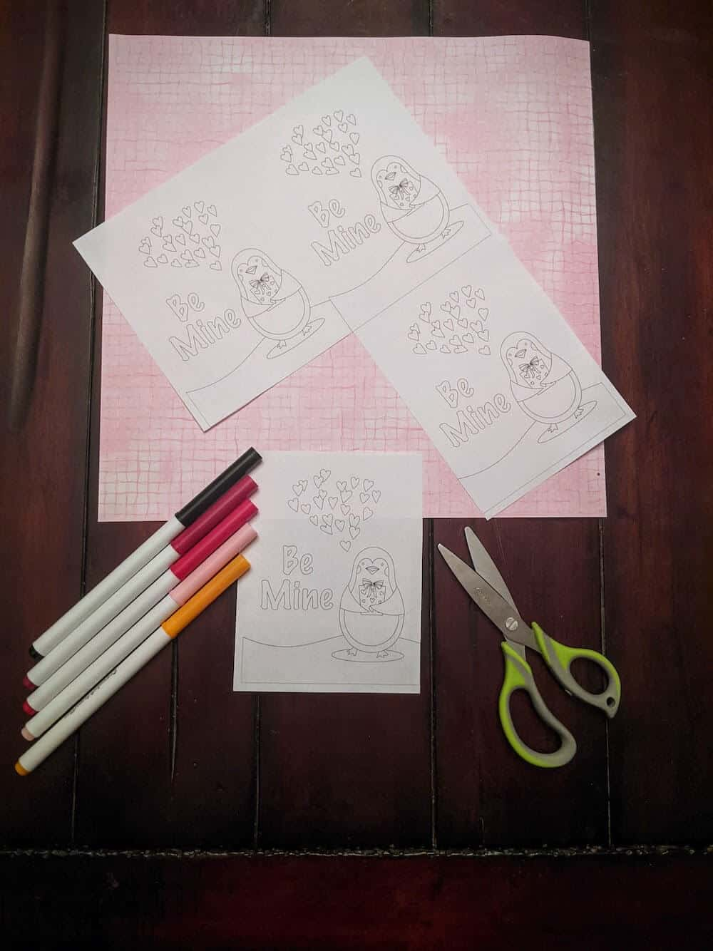Printed penguin Valentine's cards with papers, scissors, and markers ready for DIY project